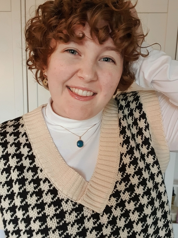 A Selfie of Vickie in a sweatervest, turtle kneck with curly hair.